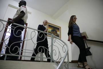 Oxfam's Ticehurst and Massot, walk to a meeting with Haiti's Minister of Planning and External Cooperation Fleurant in the Ministry in Port-au-Prince
