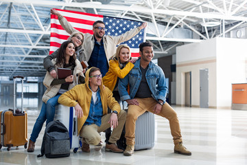 Wall Mural - Group of young people arrived at destination country. They are posing in the terminal with big american flag and smiling