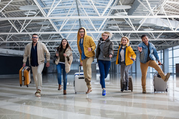 Fototapeta Full length portrait of group of tourist chasing each other at the airport. Their faces are joyous obraz
