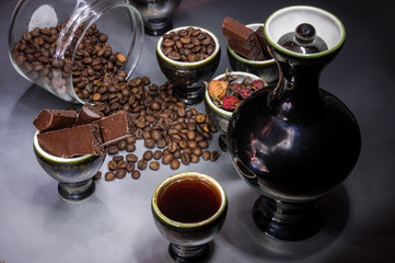 Coffee grains and chocolate in cups with coffee