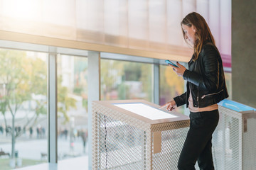 Young woman stands indoor and touches digital display while holding smartphone in her hand. Hipster girl is connected to cloud technology. Innovative technologies, digital display, urban navigation.
