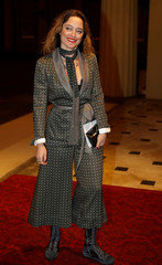 Fashion designer Temperley poses for a photograph as she arrives at the Commonwealth Fashion Exchange Reception at Buckingham Palace in London