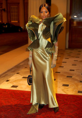 Model Campbell poses for a photograph as she arrives at the Commonwealth Fashion Exchange Reception at Buckingham Palace in London