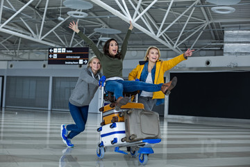 Back to the childhood. Portrait of happy women having a good time at the airport. They are rolling each other on a cart