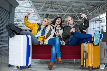 Pleased women with baggage relaxing at the airport lounge. Each of them is making selfie on smartphone