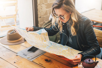 Yung woman tourist in glasses sits in cafe at table and is looking for way on destination map. Traveler girl rests in restaurant after sightseeing. On table is hat, menu and smartphone.