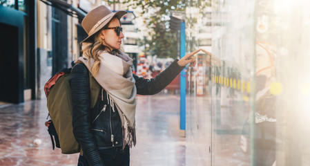 Young tourist woman in hat and with backpack stands on city street near information screen on bus stop and chooses route of trip on map. Information search, urban navigation. Travel, vacation.
