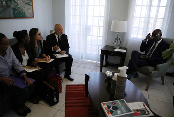 Oxfam's Ticehurst and Massot speak with Haiti's Minister of Planning and External Cooperation Aviol Fleurant at their arrival for a meeting in Port-au-Prince