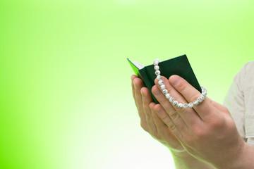 Muslim man praying holding a rosary and a Koran