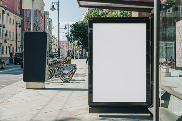 Vertical blank white billboard at bus stop on city street. In the background buildings and road. Mock up. Poster on street next to roadway. Sunny summer day. Wall mural
