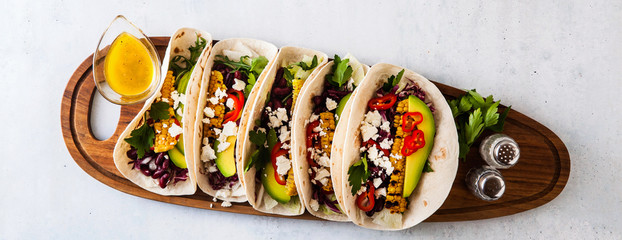 Vegetarian snack tacos with grilled vegetables, avocado, feta cheese, salad with small sweet peppers and sauce with lemon and olive oil. food background banner