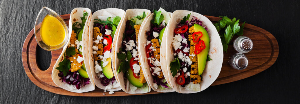 Mexican tacos with avocado, grilled corn, red cabbage slaw and chili salsa on wooden board black shale table. Recipe for Cinco de Mayo party. Top view. Copy space background banner