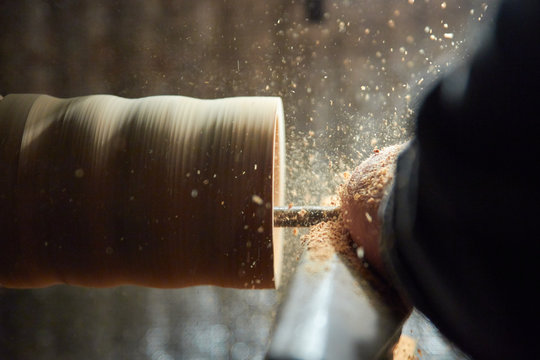 A man in the Studio hones wood blanks on a woodworking machine. turning wood on a lathe