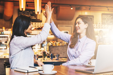 Two young business women sit in cafe at table in front of laptop and make high five. On desk notebook and cup of coffee. Girls celebrate successful transaction. Distance work, online marketing.