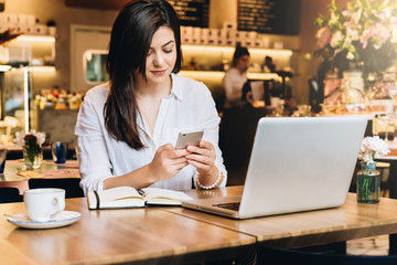 Young businesswoman sitting in cafe at table in front of laptop and using smartphone. On table notebook and cup of coffee. Online marketing, education, business planning. Distance work, e-learning.