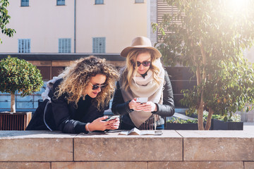 Two young women tourists are standing on city street and are looking for way on destination map and navigation system in smartphone. Girls stand leaning over map and use digital gadgets.