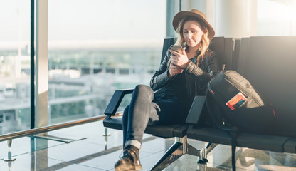 Young woman tourist in hat, with backpack sits at airport near window and uses smartphone. Hipster girl is waiting for plane landing, checks email, chatting, blogging, browsing internet.