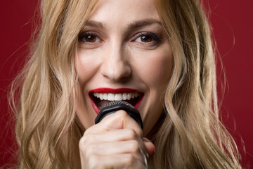Close up portrait of female expression chanting a song and looking at camera with joy. Isolated on red background