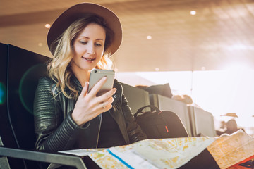 Young woman tourist in hat, with backpack sits at airport, uses smartphone, holding destination map. Hipster girl is waiting for plane landing, checks email, chatting, blogging, browsing internet.
