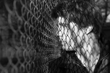 Profile of serious young man is standing and looking aside thoughtfully. His face is patterned by shadow of chain-link fence. Black and white. Copy space in the left side