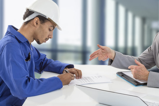 Young man apprentice contract signature over an open space interior with large windows background