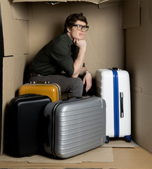 Where is my flight concept. Full length of confused guy is sitting with his luggage inside confined cardboard box. He is looking aside disappointedly while waiting for departure