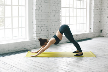 Full length view of flexible young woman with slim fit body working out in fitness center hall, doing yoga, exercising with mat on wooden floor, doing downward facing dog or adho mukha svanasana pose