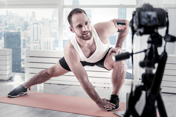 Touch your toe. Attractive appealing male blogger stretching his muscles while filming video and exercising on mat board