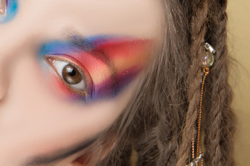 Close-Up Part of face of Model with colorful abstract makeup and dreadlocks hairstyle.
