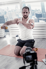 For biceps. Attentive bearded male blogger sitting on mat board while rising dumbbell and pointing at muscle