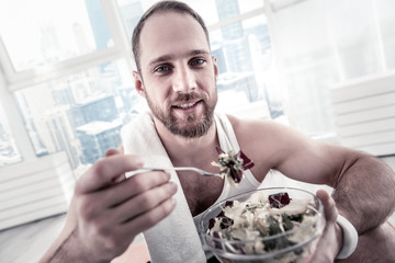 Fast making salad. Sincere strong glad sportsman consuming salad for receiving vitamins and staring at camera