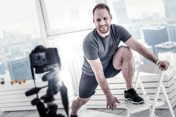 Excellent motivation. Cheerful pretty male blogger putting leg on chair while showing technique and smiling