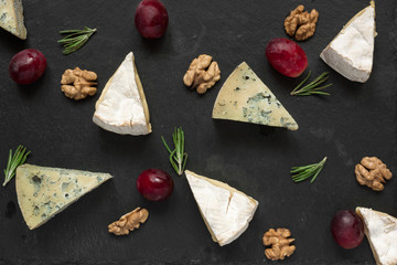 camembert or brie and blue cheese slices with grapes, walnuts, and of rosemary on black slate background