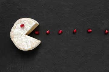 Camembert or brie cheese cut out like pacman eating pomegranate seeds on black slate background