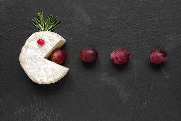 Camembert or brie cheese cut out like pacman eating grapes on black slate background