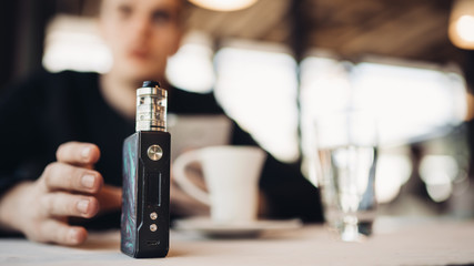 Using electronic cigarette to smoke in public places.Smoke restriction,smoking ban.Using vaping device with flavoured liquid.E-juice vaping new technology.Give up tobacco.Smoking habit,nicotine addict Wall mural