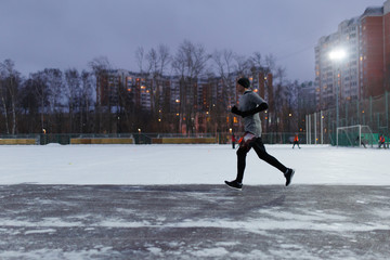 Photo of athlete in black sports clothes running in winter park