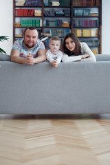 Picture of happy woman and man with boys on gray sofa