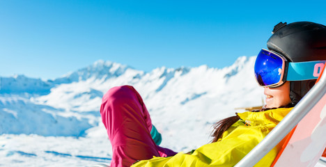 Picture of sports woman in helmet sitting at snowy resort