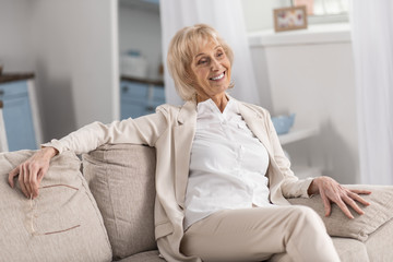 Relaxing posture. Pleasant positive mature woman relaxing on couch while smiling and holding glasses
