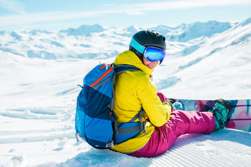 Picture from back of woman in helmet with backpack sitting on snow with snowboard