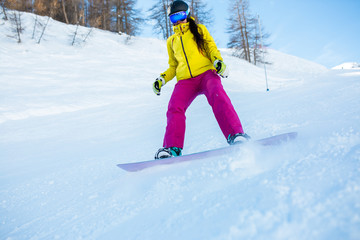 Picture of athletic woman wearing helmet and mask snowboarding from snowy slope with trees