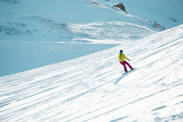 Photo of sports girl wearing helmet and mask, snowboarding from mountain slope