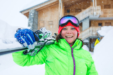 Woman in helmet with skis on shoulder on background of wooden building