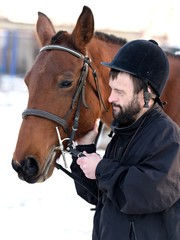Down syndrome man with horse. Hippotherapy