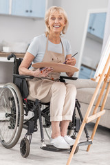 Happy life. Disabled mature nice woman posing in wheelchairs while grinning and carrying pallet and tassel