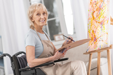 My hobby. Mature disabled cheerful woman smiling while staring at camera and painting in wheelchair