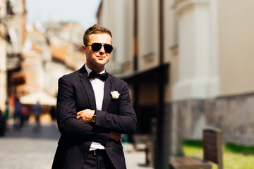 stylish groom in a beautiful costume in sunglasses against the b