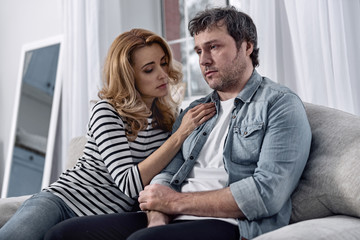 Showing support. Kind attentive loving wife putting her hand on a chest of her depressed unshaved husband while sitting next to him on a soft sofa and demonstrating her care