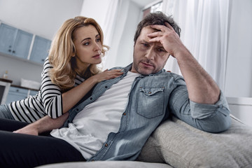Calm down. Tired depressed unemployed man sitting on a sofa and thoughtfully touching his forehead while his caring loving wife looking attentively at him